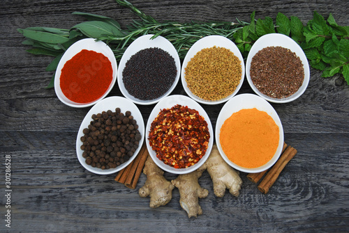 assortment of hearbs and spices on rustic wood