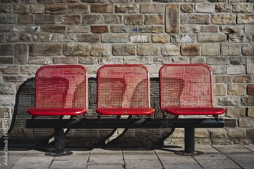 Photo Beautiful shot of three red seats in the bus station of an urban area