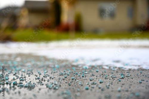 Fotografie, Obraz  Ground level closeup view of rock salt ice-melt  on concrete with snow