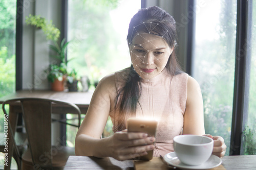 Beautiful young asian woman in the cafe, using mobile phone and drinking coffee smiling Canvas Print