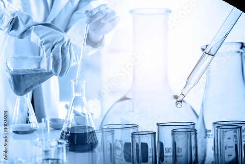 Stampa su Tela hand of scientist holding flask with lab glassware and test tubes in chemical la