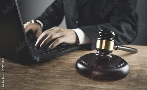 Judge working with computer on wood table. Slika na platnu