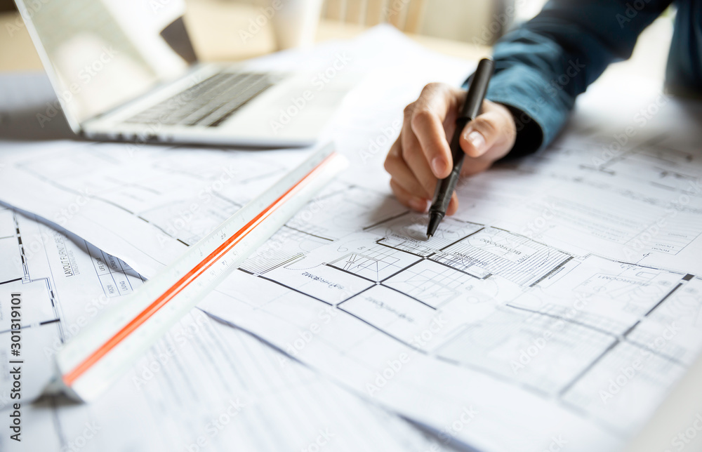 Fototapeta Close up woman hand working of Architect sketching project on blueprint at site construction work. Concept of architect, engineer in the office desk construction project