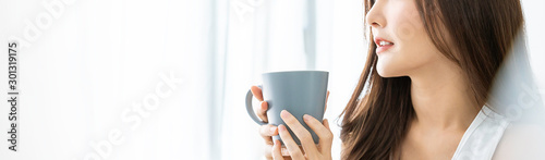 Portrait of young beautiful asian woman hands holding coffee cup morning spring time in white bedroom Tapéta, Fotótapéta