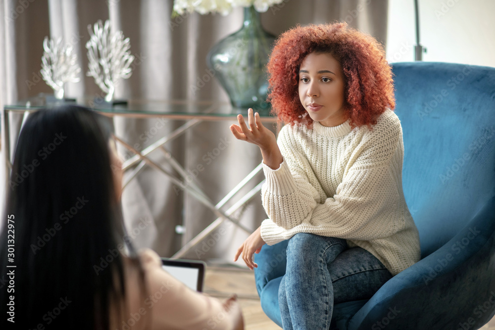 Fototapeta Young woman wearing jeans speaking with psychologist