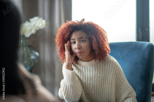 Fotomural Young woman feeling concerned while having psychoanalysis