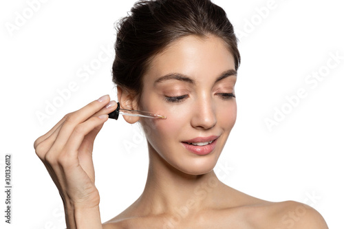 Fotografía  Close up  portrait of brunette girl using skincare cosmetic oil with pipette