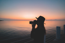 Silhouette Of Woman Photographer In Hat With Digital Camera During Taking Photos Of Sea At Pier At Sunset