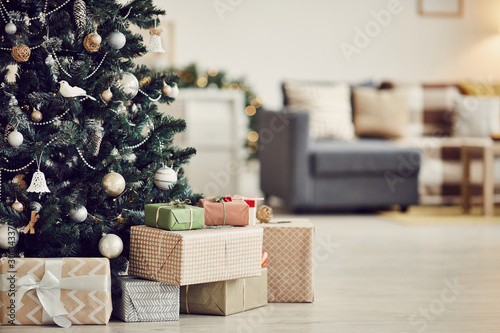Fototapeta Image of decorated Christmas tree with gift boxes under it on the floor in the living room obraz