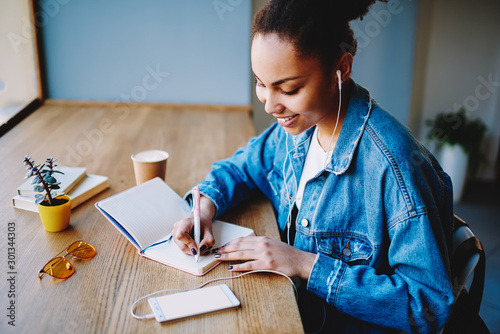 Happy african female meloman listening positive romantic playlist via electronics headphones and media application on cellular phone while writing university essay with excited idea in notebook - 301344303