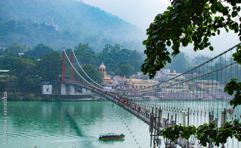 Fototapety, obrazy: beautiful view of Rishikesh in India 'ram jhula' and 'lakshman jhula' suspension bridge beautiful scenery with boat in the river ganges in lake in the mountains of Himalayas tourism attraction in Asia