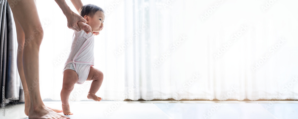 Fototapeta Asian baby taking first steps walk forward on the mat. Happy little baby learning to walk with mother help at home. Mother teaching how to walk gently. Baby growth and development concept. Banner size