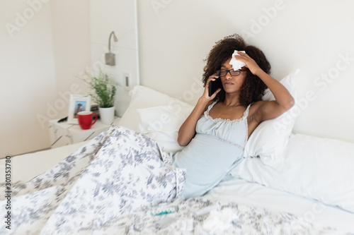 Young woman suffering from a cold or a flu takes her temperature with a thermometer in bed Canvas Print