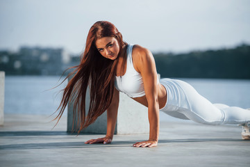 Shot of sportive woman doing fitness exercises near the lake at daytime