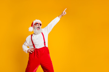 Fototapeta na wymiar Portrait of funny crazy santa claus hipster in red hat fun christmas x-mas party celebrate newyear time dance raise index finger wear shirt suspenders isolated yellow color background