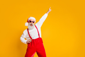 Fototapeta na wymiar Christmas party hard. Portrait of crazy funny santa claus hipster in red hat enjoy x-mas noel celebration dance raise index finger wear shirt suspenders isolated yellow color background