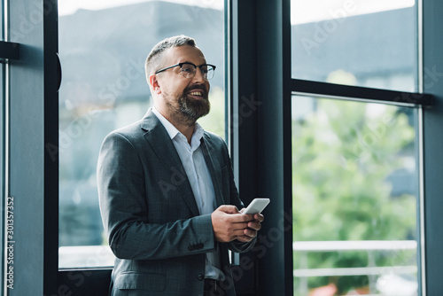 Fototapety, obrazy: handsome businessman in formal wear and glasses holding smartphone