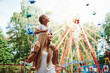 canvas print picture - Daughter sits on the shoulders. Cheerful little girl her mother have a good time in the park together near attractions