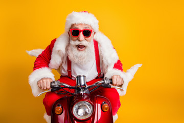 Fast x-mas traveling. Crazy funky hipster grey haired santa claus in red hat drive scooter hurry scream wear shirt suspenders isolated over bright color background
