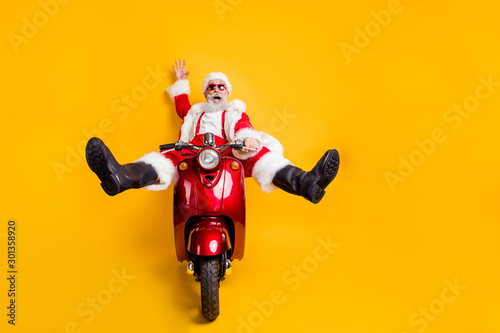 fototapeta na ścianę Full size photo of amazed funny crazy santa claus in red hat drive fast scooter want hurry on x-mas christmas party shirt suspenders isolated over yellow color background