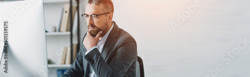 panoramic shot of handsome businessman in formal wear and glasses looking at computer