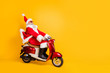 canvas print picture - Full body photo of santa white hair grandpa riding speed x-mas party by bike afraid to be late wear trendy sun specs red coat trousers cap shirt boots isolated yellow color background