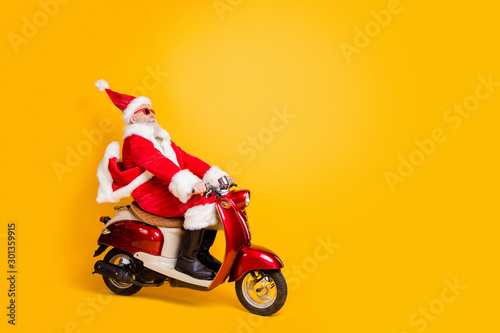 Full length profile photo of santa white hair grandpa riding speed x-mas party by bike wear trendy sun specs red coat trousers cap shirt boots isolated yellow color background