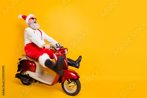 fototapeta na szkło Full body photo of crazy santa white hair grandpa rushing x-mas party speed by retro bike wear trendy sun specs red trousers cap shirt boots isolated yellow color background