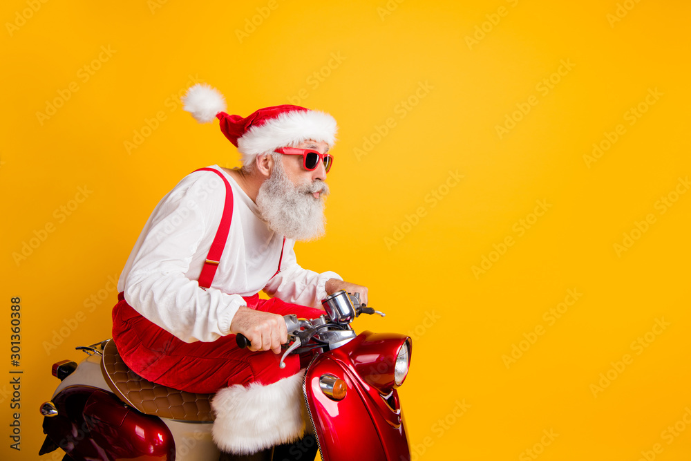 Fototapety, obrazy: Profile photo of stylish santa white hair grandpa riding speed x-mas theme party by bike wear trendy sun specs red trousers cap shirt boots isolated yellow color background