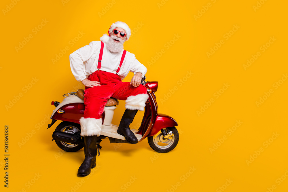 Fototapety, obrazy: Full size photo of funny santa aged man in festive mood ready for x-mas theme party sitting on vintage bike wear sun specs pants cap shirt boots isolated yellow color background