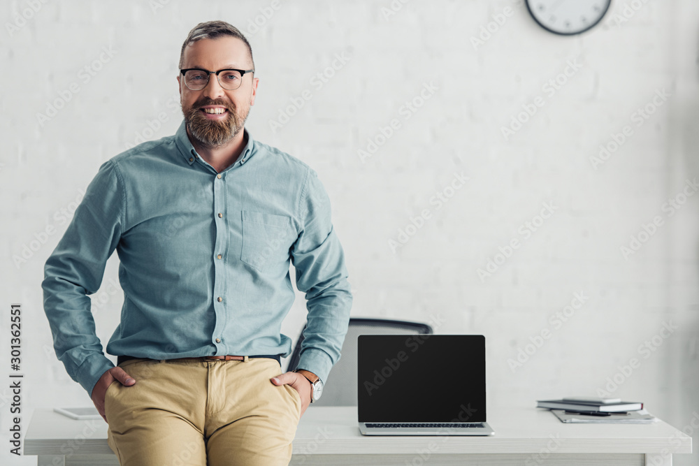 Fototapeta handsome businessman sitting on table near laptop with copy space