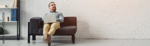 panoramic shot of handsome businessman in shirt holding laptop and looking away