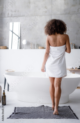 Young woman in towel going to take bath Fototapet