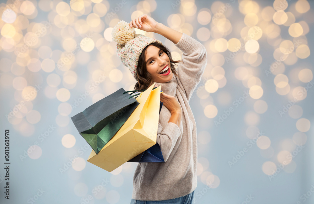 Fototapeta christmas, seasonal sale and consumerism concept - happy smiling young woman in knitted winter hat and sweater with shopping bags over festive lights background