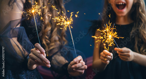 Obraz Mother and daughter lit sparklers on Christmas night. Selective focus. - fototapety do salonu