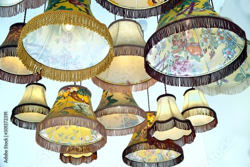 Photo Antique or vintage lampshades hanging in a display group
