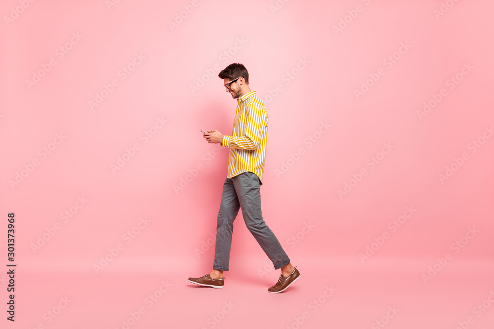 Fototapeta Full size profile photo of handsome guy going street finished working week typing girlfriend sms telephone wear specs striped shirt pants isolated pink color background