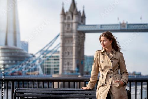 Fotografía Attraktive Geschäftsfrau im Trenchcoat steht vor der Skyline von London, Großbri