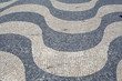 A beautifully designed floor with black and white Portuguese stones in the port area by the Tagus river, Lisbon, Portugal.