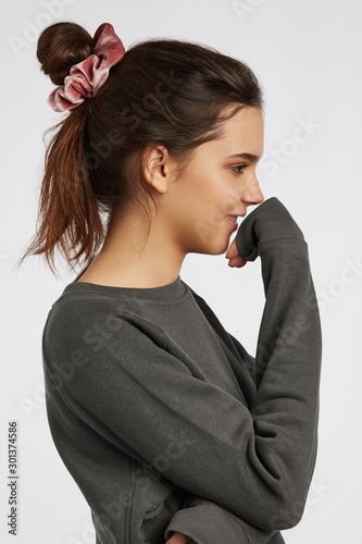 Profile portrait photo of a dark-haired girl, posing on a white background Slika na platnu