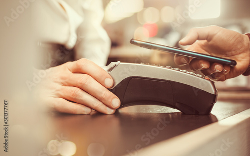Customer hand pays with smartphone in store using NFC technology Fototapete