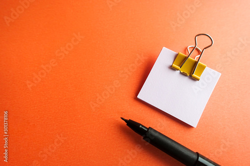 Fotografía  Pen, yellow paper clip and blank paper on a orange background