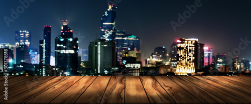 фотография top wood desk with urban city night view blur background,wooden table