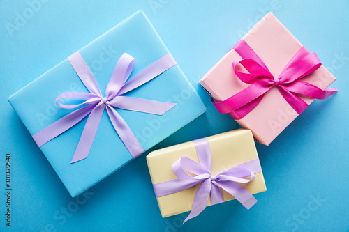 top view of colorful gift boxes on blue background