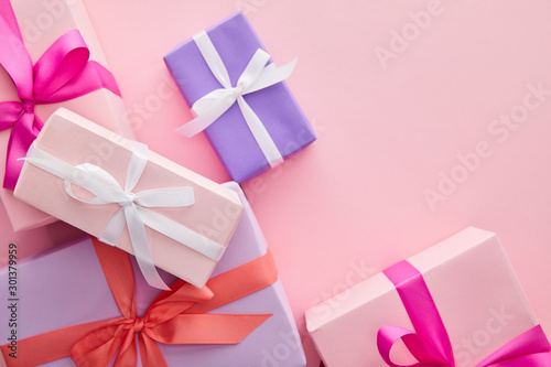 top view of colorful gift boxes with ribbons and bows scattered on pink background