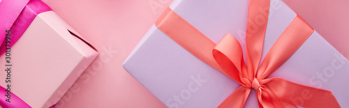top view of colorful gift boxes with ribbons and bows on pink background, panoramic shot
