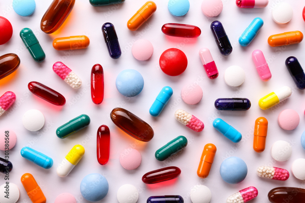 Obraz Flat lay composition with bunch of different colorful pills in scattered all over the table. Pile of opened medication on paper textured background. Close up, copy space. fototapeta, plakat