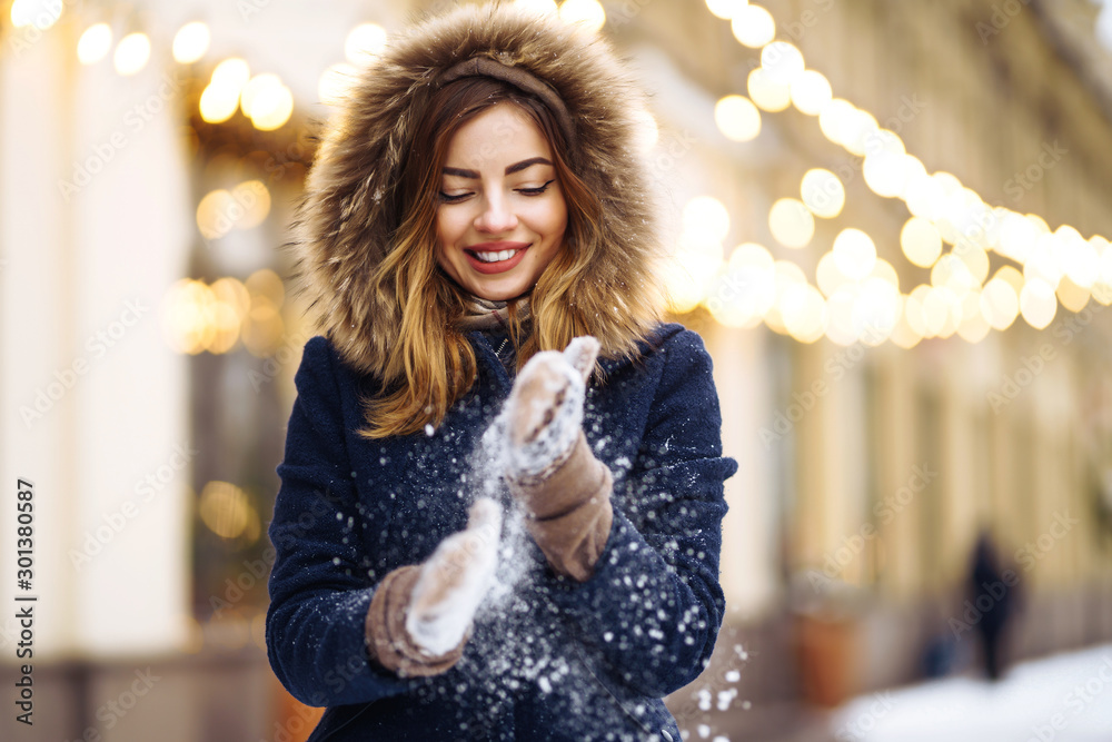 Fototapeta Beautiful  girl in a blue jacket and knitted hat and mittens posing in street of city. Garland lights. Enjoying snow, smiling to camera, cheerful  new year mood, true emotions. Winter fashion.
