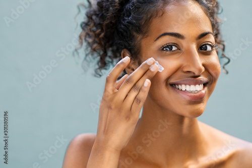 Woman applying moisturizer on face Wallpaper Mural