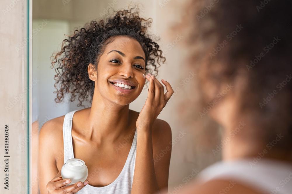 Fototapety, obrazy: Black girl applying lotion on face